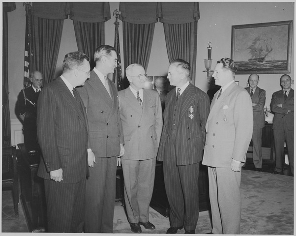 President Truman in the oval office with four men who received the Medal of Merit. John Kennedy