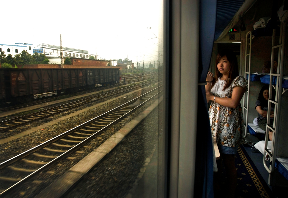 Woman inside a train from Beijing to Chengdu, China.