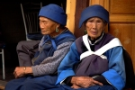 Two women rest in the sidewalk. Southwest China