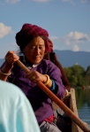 Woman rowing a boat for tourists in Lugu Lake, Sichuan Province, China..